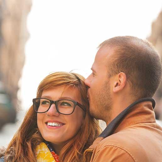Man kissing woman's hair